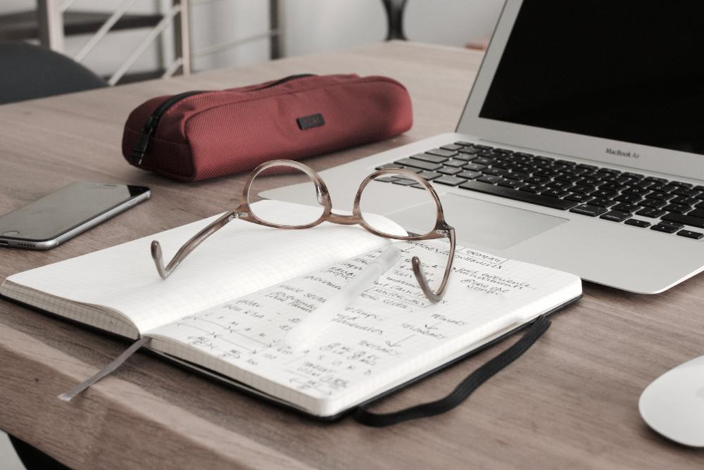 Glasses on notebook by laptop