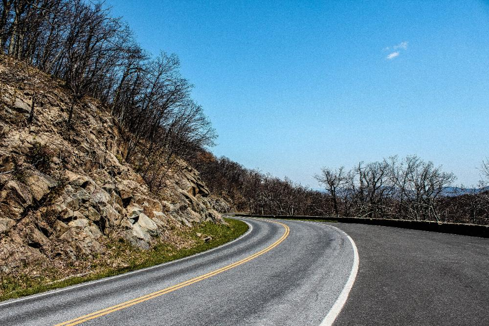 A road turning around a rocky bend in the mountains