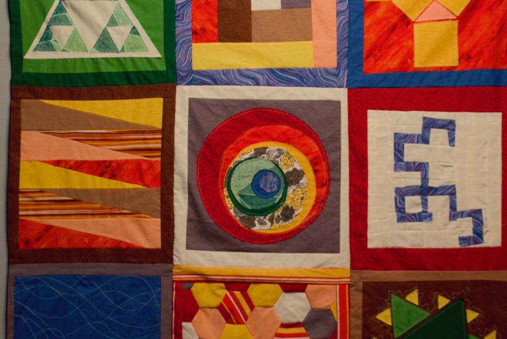 colorful quilted artwork depicting geometric shapes