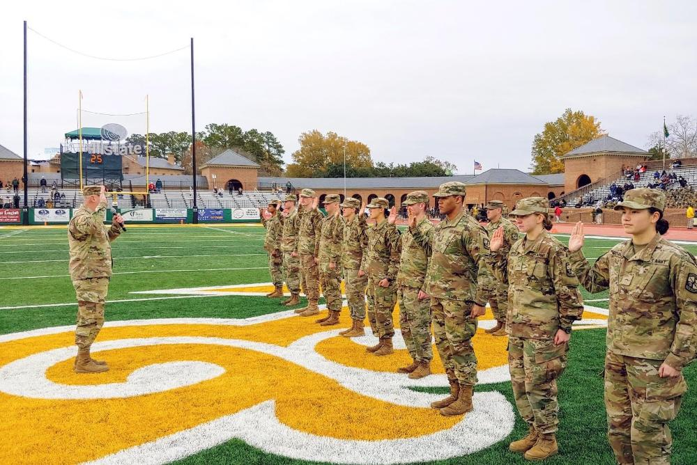U.S. Army soldiers stand on the W&M football field with their right hands raised as a military official leads them through a promotion ceremony.