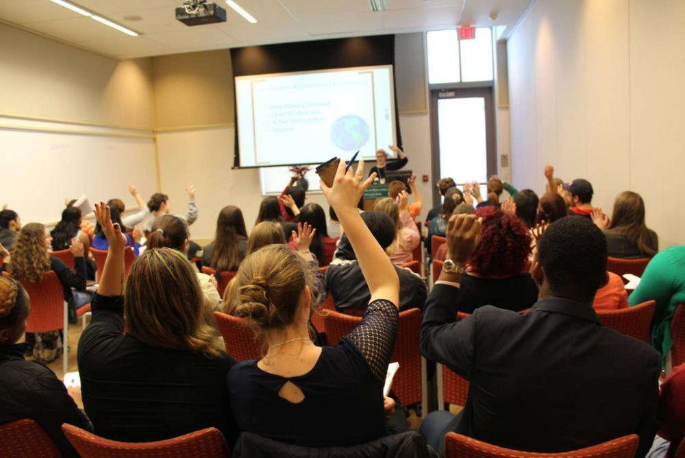 Conference attendees raising their hands during a workshop