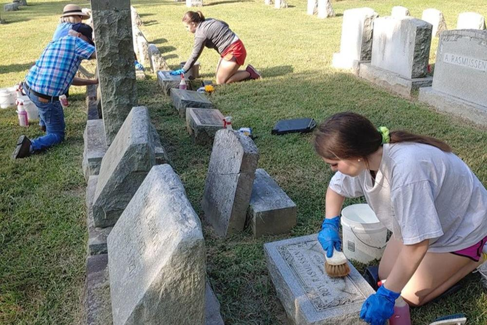 Volunteers cleaning cemetery markers
