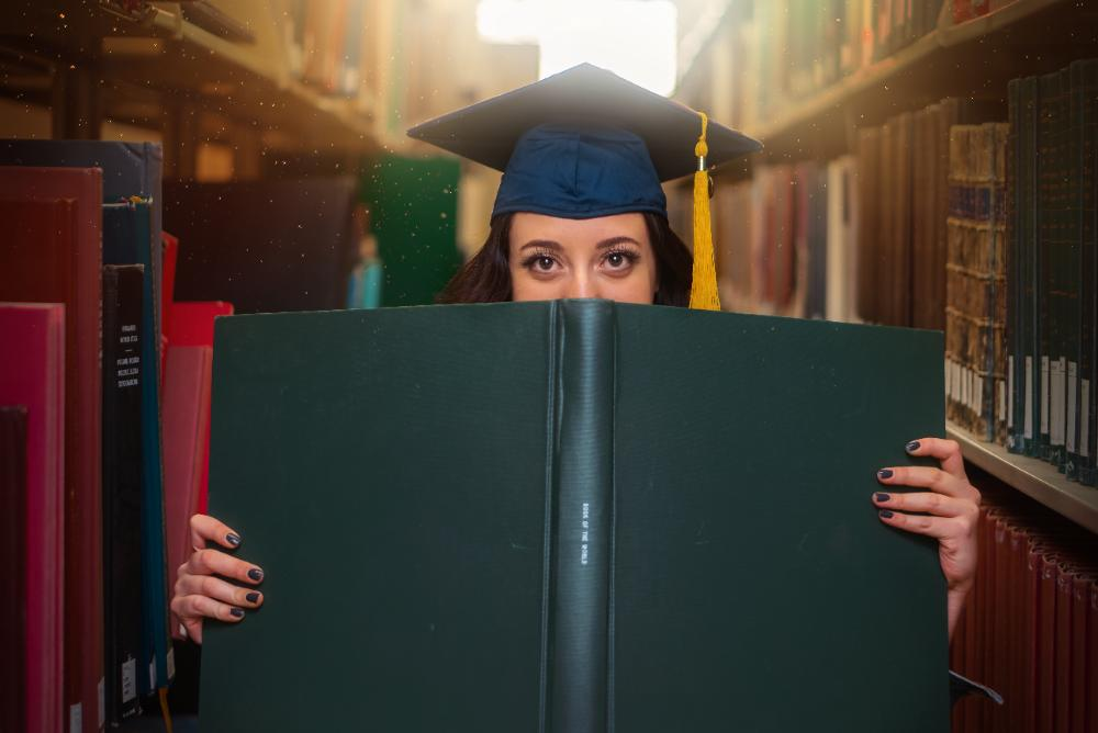 woman in graduation cap and gown holding a dissertation in the library