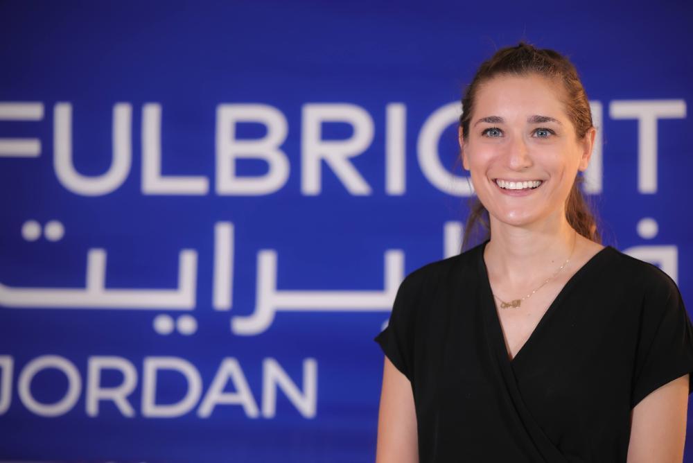 headshot, woman, black top, fulbright, blue background, smiling