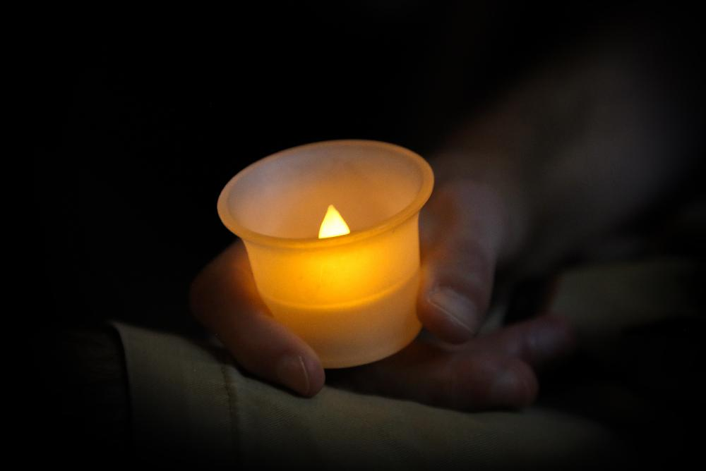 Electric tealight candle, lit and held in the palms of a pair of hands.