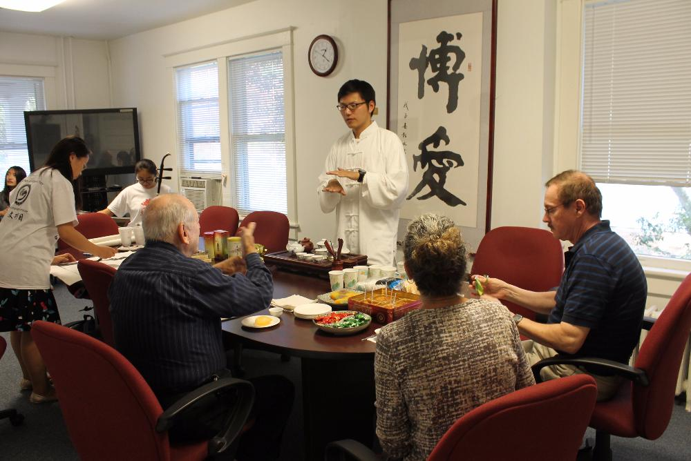 House Tutor Xu Han explains the cultural significance of the tea ceremony to a community member.