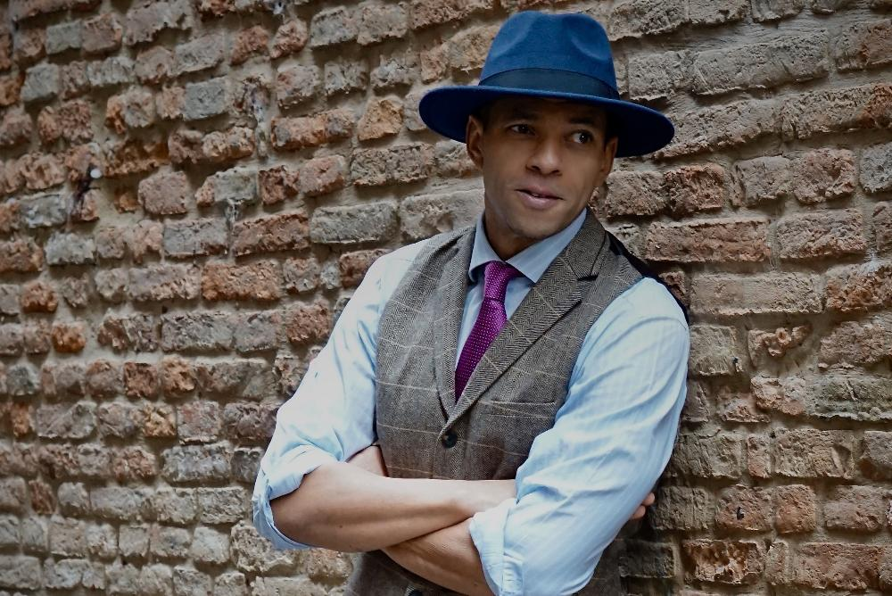 Speaker Fred Kuwornu leans against a brick wall with arms crossed, dresed in fedora and vest.