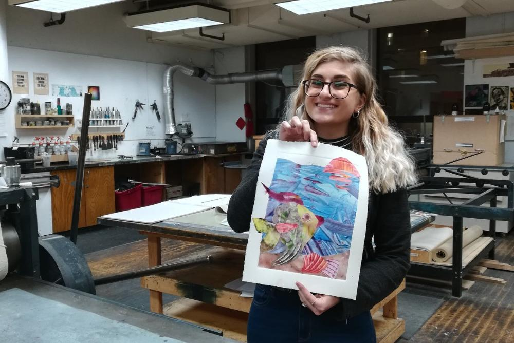 A student holds up her work from a prior Monoprint Workshop with Steve Prince