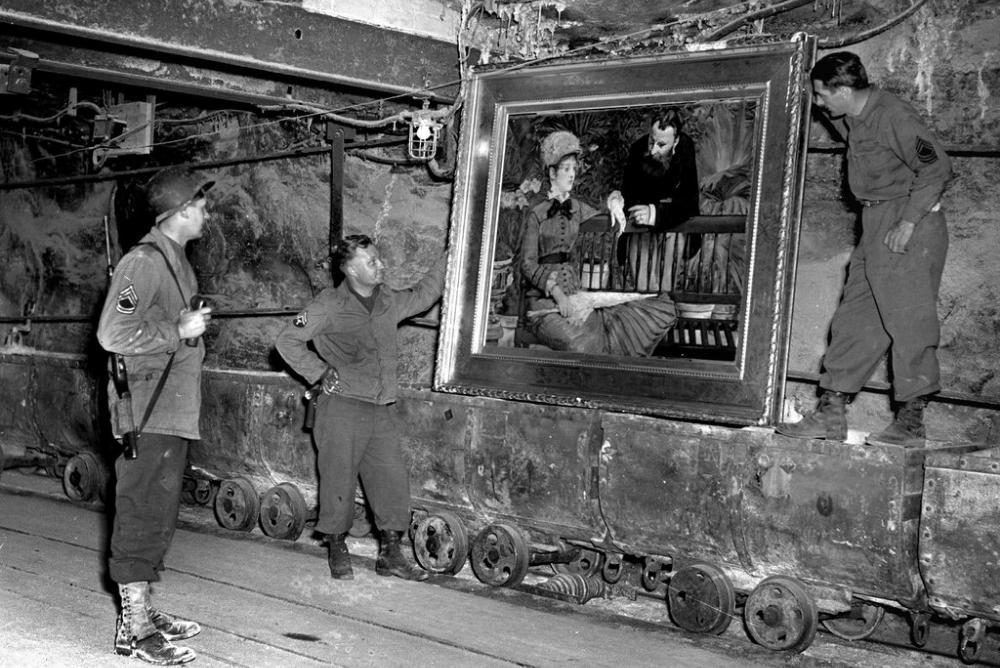"""American soldiers look at """"In the Wintergarden,"""" by Edouard Manet, at a mine in Germany where the Nazis stored looted artwork. National Archives and Records Administration, Washington, D.C."""