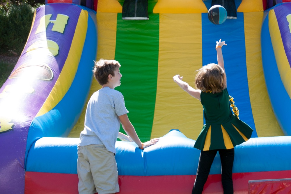 Two children playing an inflatable game of basketball