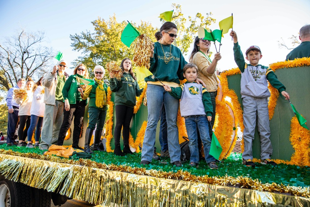 Homecoming parade float participants cheer in their green and gold