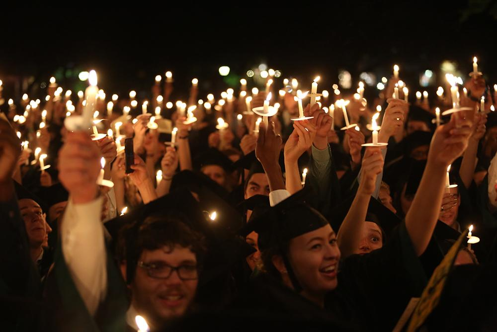outside, outdoors, people, students, traditions, candlelight ceremony, night, candles, commencement, graduation, seniors, regalia, hands, mortar boards