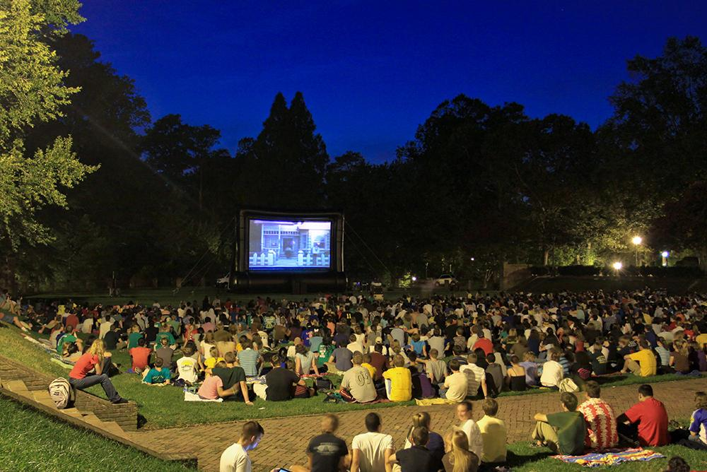students, outdoors, outside, people, sunken garden, screen on the green, trees, projection, movies, media, night
