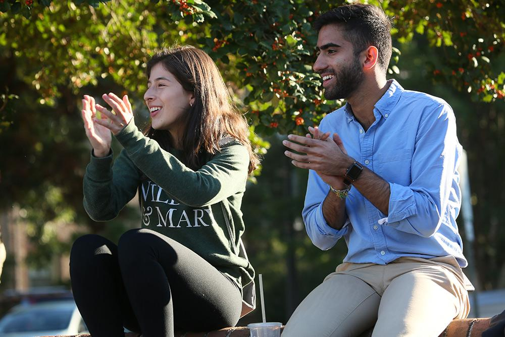 Two students clapping outdoors